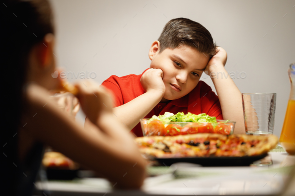 Mother Giving Salad Instead Of Pizza To Overweight Son - Stock Photo - Images