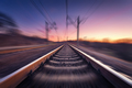 Railway station at colorful sunset with motion blur effect. Rail - PhotoDune Item for Sale