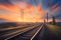 Railroad in motion at sunset. Blurred railway station - PhotoDune Item for Sale