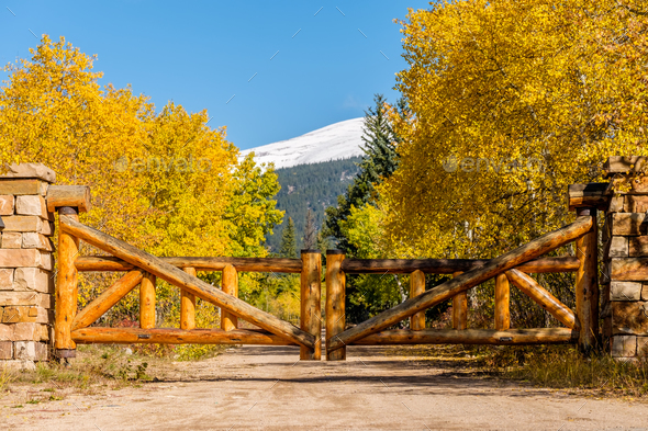 Rustic gate made of logs on unpaved road - Stock Photo - Images