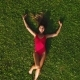 Aerial: Beautiful Girl Lies on the Green Grass and Posing on the Camera. - VideoHive Item for Sale