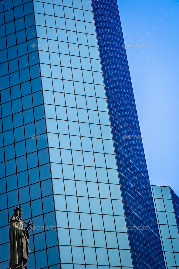 Statue of holy Mary in front of modern glass office building in - Stock Photo - Images