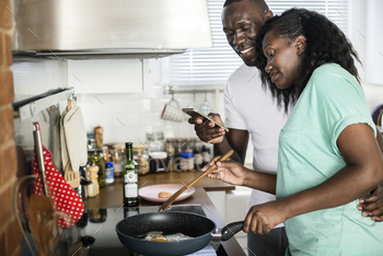 Couple cooking fried eggs in the kitchen