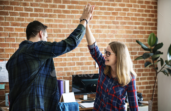 Caucasian colleagues give each other high five