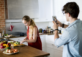 Man taking a photo of his wife in the kitchen