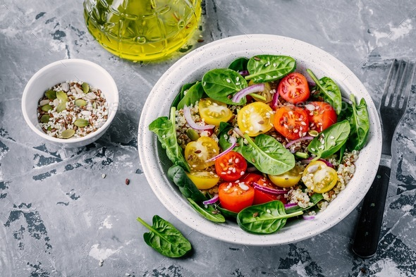 Healthy green salad with spinach, quinoa, yellow and red tomatoes, onions and seeds - Stock Photo - Images
