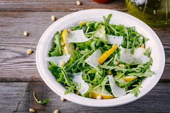 green salad bowl of arugula with pear, parmesan cheese and pine nuts - Stock Photo - Images