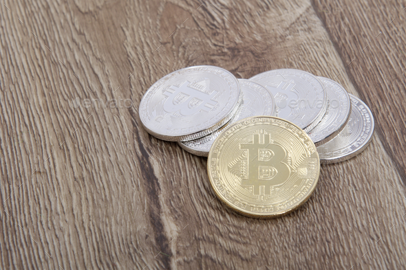 Silver bitcoins and one gold on a table - Stock Photo - Images
