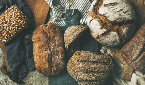 Flat-lay of various bread loaves, top view, wide composition - Stock Photo - Images