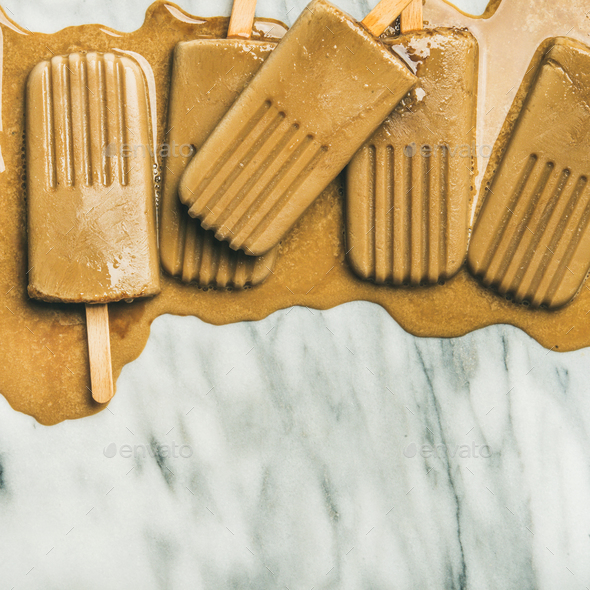 Flatlay of melting coffee latte popsicles, square crop - Stock Photo - Images