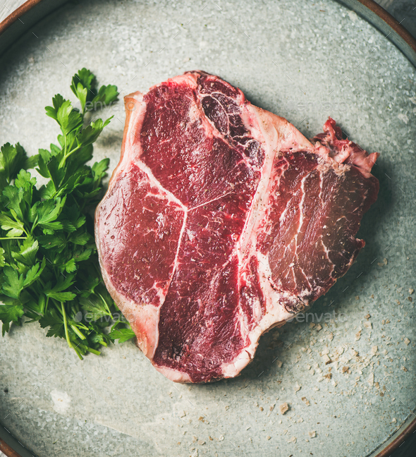 Flat-lay of raw uncooked dry-aged t-bone prime beef steak - Stock Photo - Images