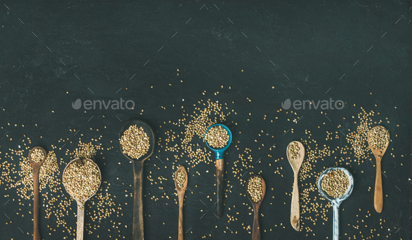 Various vintage kitchen spoons full of green buckwheat grains - Stock Photo - Images
