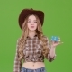 Cowgirl in a Hat Shows Her Finger on the Card, She Advertises the Goods. Green Screen - VideoHive Item for Sale