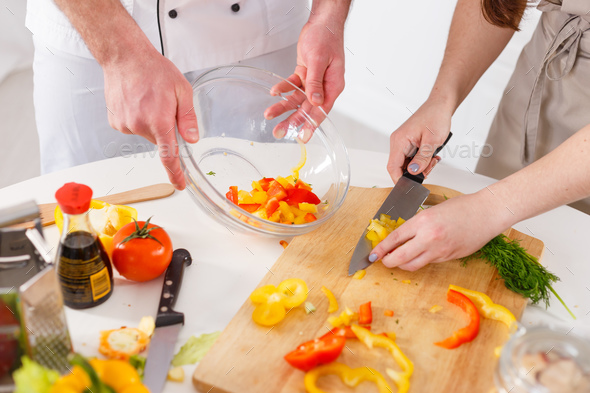 Woman mixing a salad with professional cook in the kitchen - Stock Photo - Images