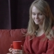 Cute Young Smiling Girl in Red Sweater Enjoying Her Coffee at Home - VideoHive Item for Sale