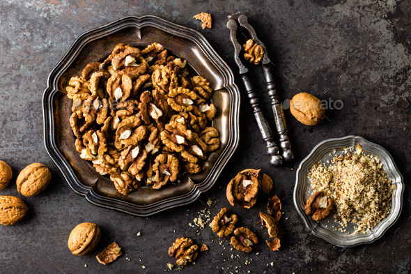 Walnut kernels and whole walnuts on rustic old wooden table - Stock Photo - Images