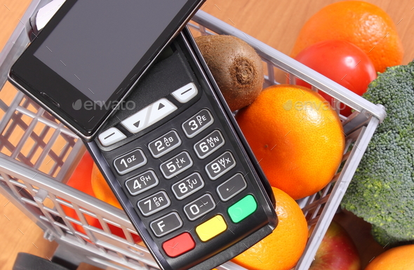 Payment terminal and mobile phone with NFC technology, fruits and vegetables - Stock Photo - Images