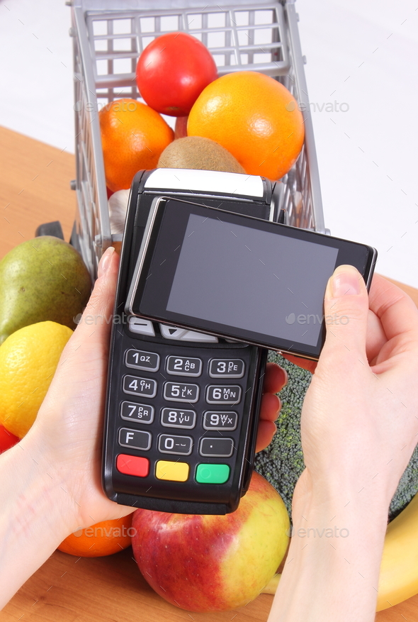 Credit card reader and mobile phone with NFC technology, fruits and  vegetables