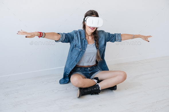 Flying girl while using VR glasses - Stock Photo - Images