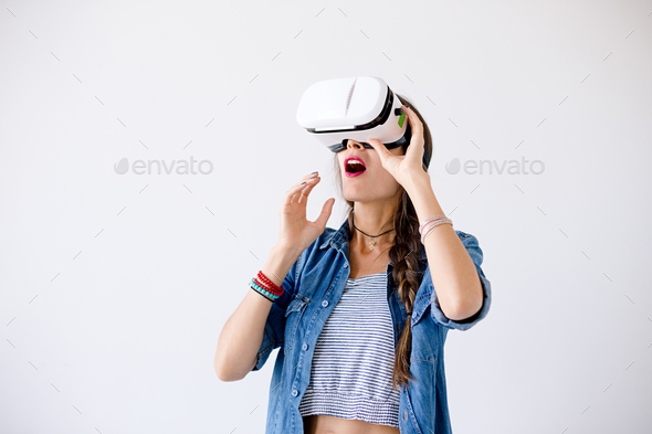 Excited girl with VR glasses in studio - Stock Photo - Images