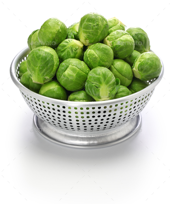fresh brussels sprouts in colander isolated on white background - Stock Photo - Images