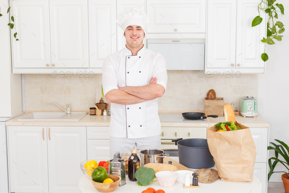 Smiling chef cooking vegetarian healthy meal - Stock Photo - Images