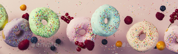 Sweet and colourful doughnuts falling or flying in motion - Stock Photo - Images