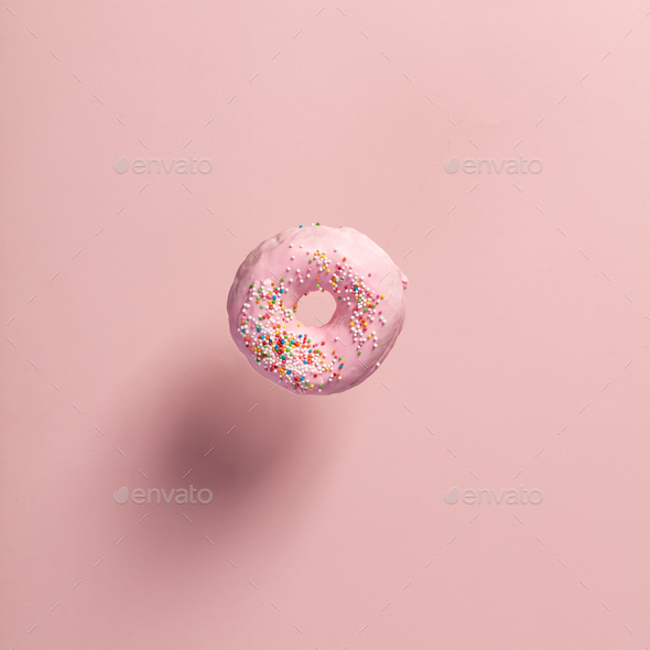 Pink doughnut with sprinkles falling or flying in motion - Stock Photo - Images