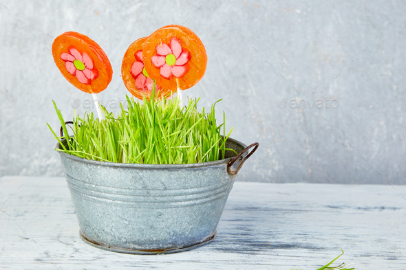 Spring concept. Candy lollipop flower in flowerpot with grass - Stock Photo - Images