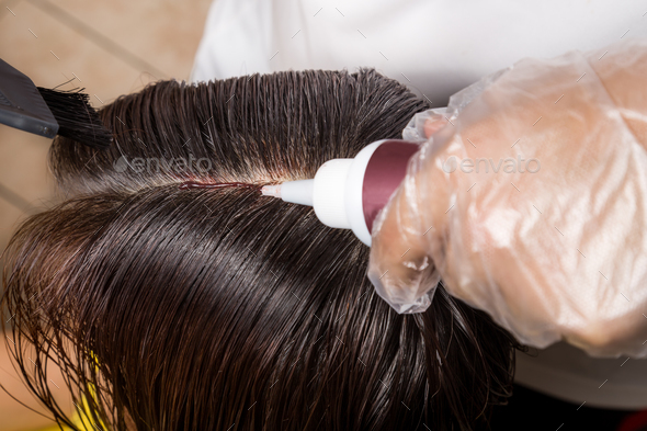 Hair dresser applying chemical hair color dye onto hair roots - Stock Photo - Images