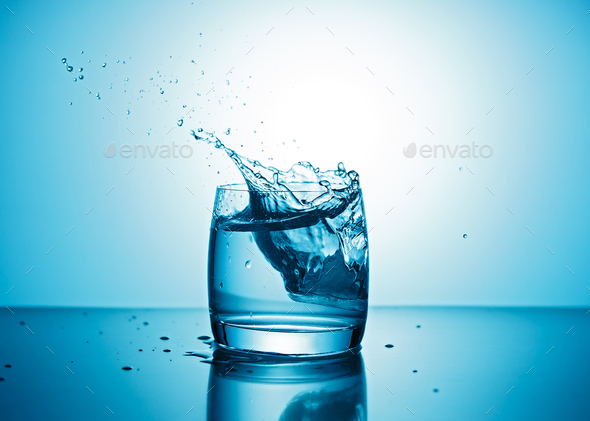 Pure water splashing out of glass - Stock Photo - Images
