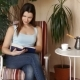 Young Attractive Woman Reading Interesting Book while Sitting on Comfortable Chair - VideoHive Item for Sale
