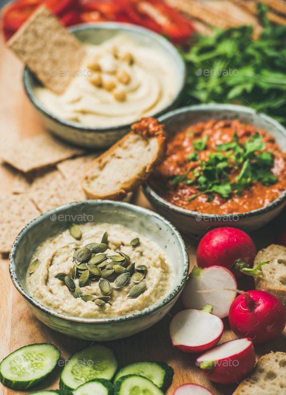 Vegetarian dips hummus, babaganush, muhammara over wooden background - Stock Photo - Images