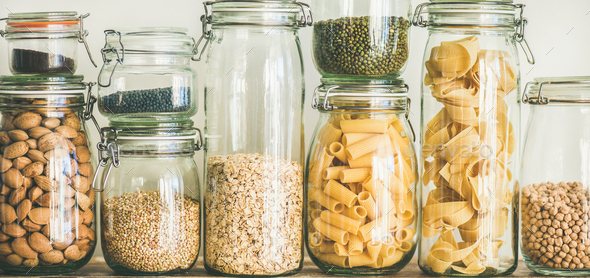 Uncooked cereals, grains, beans and pasta on rustic table, close-up - Stock Photo - Images