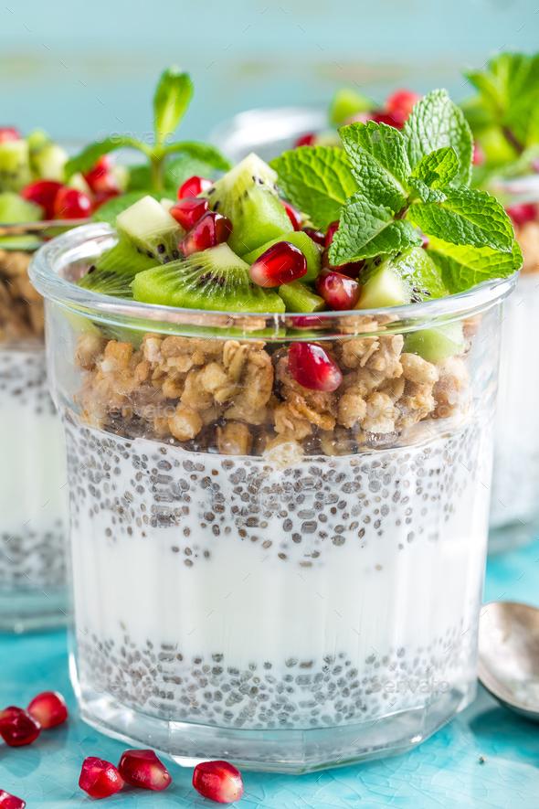 Layered chia pudding parfait with kiwi fruit, pomegranate, granola and yogurt, healthy breakfast - Stock Photo - Images