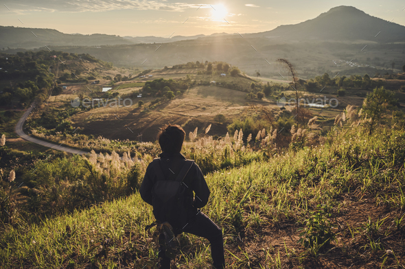 Young traveler looking at sunrise over the mountain - Stock Photo - Images