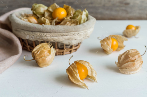 Cape gooseberry fruit in basket on white wooden table - Stock Photo - Images