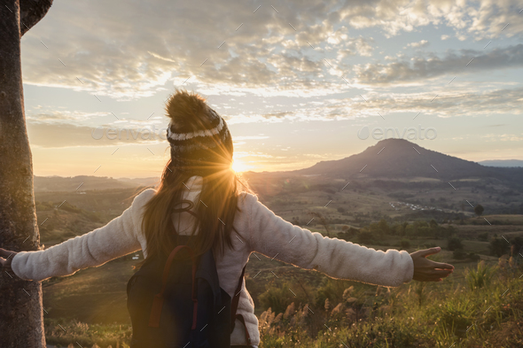 Cheering young woman traveler looking at sunrise - Stock Photo - Images
