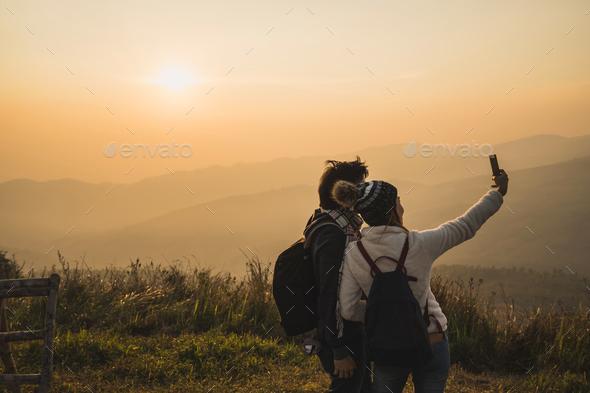Loving couple traveler making selfie with beautiful sunset - Stock Photo - Images