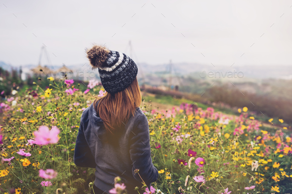 Young woman traveler walking in the flower field - Stock Photo - Images
