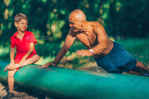 Grandfather and grandson  exercising in park - Stock Photo - Images