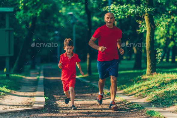 Grandfather and grandson jogging in park - Stock Photo - Images