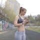 Evening Jog Pretty Young Girl with Headphones Selects Music - VideoHive Item for Sale