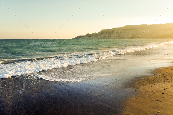 Sea waves and sandy beach at sunset. Toned and saturated image - Stock Photo - Images