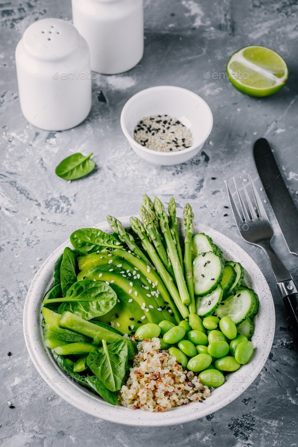 Green vegetarian bowl salad with quinoa, spinach, avocado, asparagus, cucumber, edamame - Stock Photo - Images
