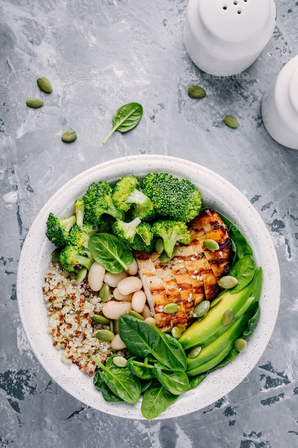 Green buddha bowl lunch with grilled chicken and quinoa, spinach, avocado, broccoli and white beans - Stock Photo - Images