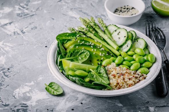 Green bowl salad with fresh vegetables and quinoa, spinach, avocado, asparagus, cucumber, edamame - Stock Photo - Images