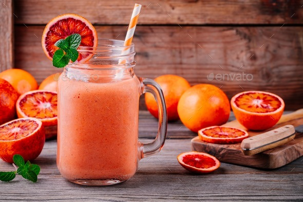 Fresh smoothie with  banana, blood oranges and mint in a mason jar - Stock Photo - Images