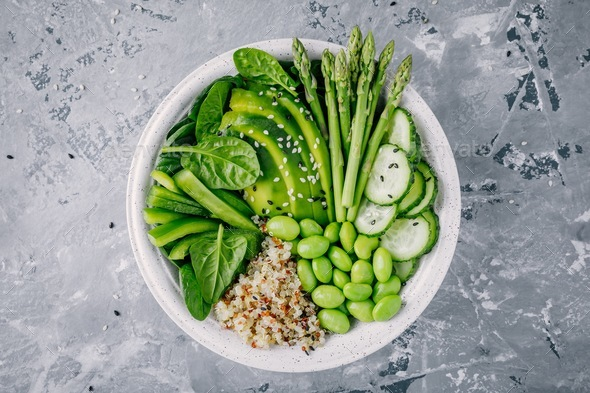 Green vegetarian bowl with quinoa, spinach, avocado, asparagus, cucumber, edamame - Stock Photo - Images