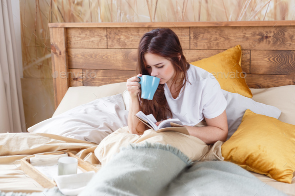 Cute girl on a comfortable chair with tea ,reading a book, the concept of comfort and hipster. - Stock Photo - Images